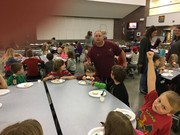 Custodian, Mr. Blank, putting bunny ears on a student in the lunchroom